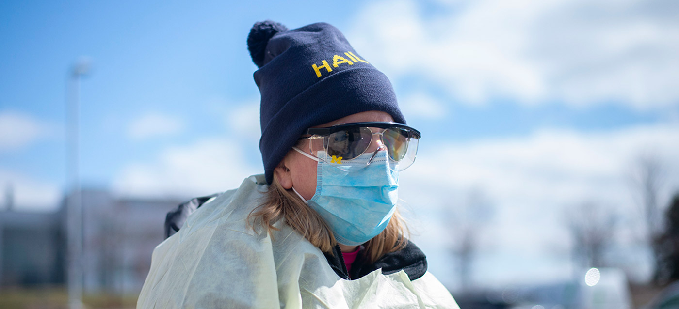 Person in face mask wearing HAIL beanie