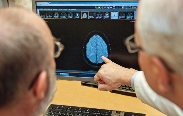 Two people looking at an image of a brain